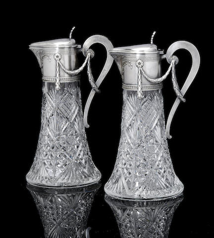 A pair of silver mounted cut-glass claret jugs