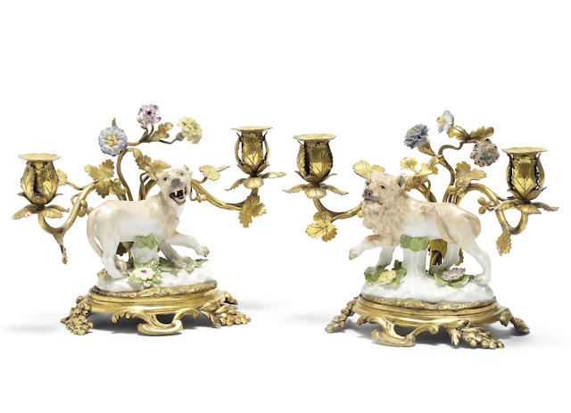 A pair of Meissen models of lions mounted on ormolu candelabra