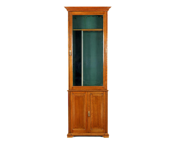 A late Victorian oak gun cabinet by Army & Navy C.S.L.