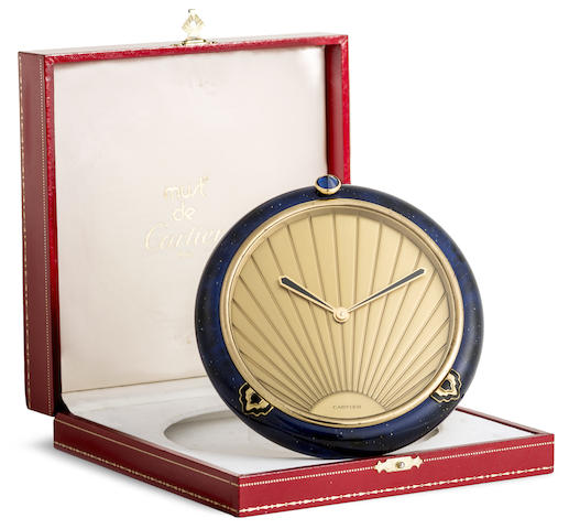 Cartier. A round gilt and blue lacquer quartz timepiece with box and paper