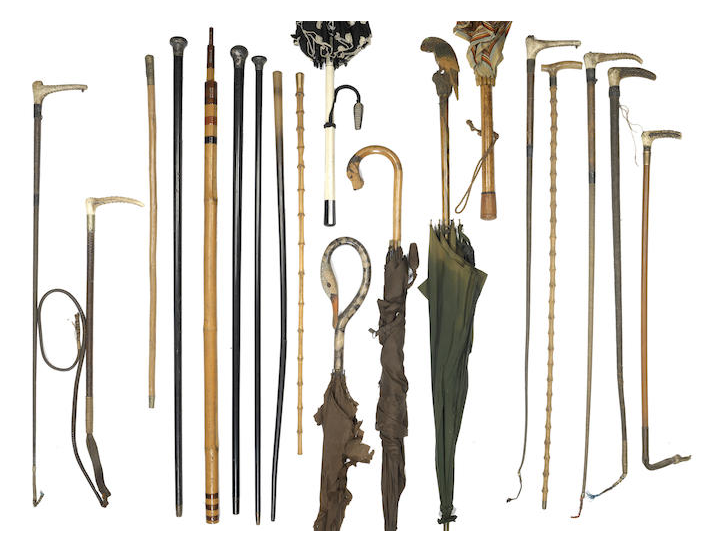 A collection of sticks, parasols and riding crops together with a large brass and copper water jug