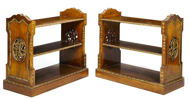 A pair of George II style parcel gilt walnut open bookcases