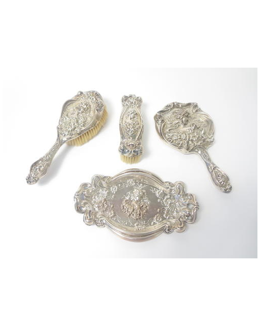 An Art Nouveau four piece silver mounted dressing table set