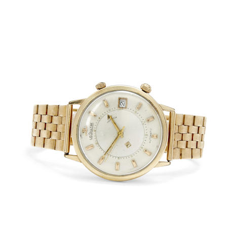 A 10K gold center seconds alarm wristwatch with date and a 14K gold bracelet