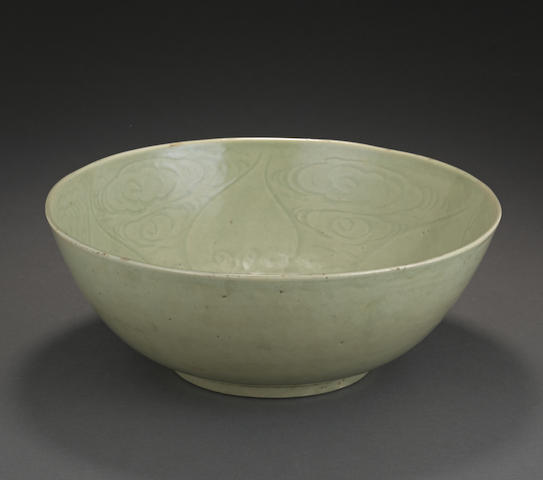 A large celadon glazed bowl with incised decoration