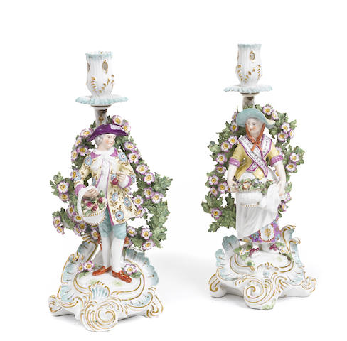 A pair of French porcelain figural candlesticks in the Chelsea style