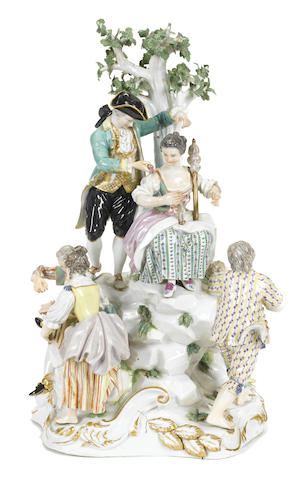 A German porcelain figural group modeled as figures at play before a tree