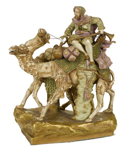 A Continental porcelain figural group modeled as a Bedouin riding a camel accompanied by another camel
