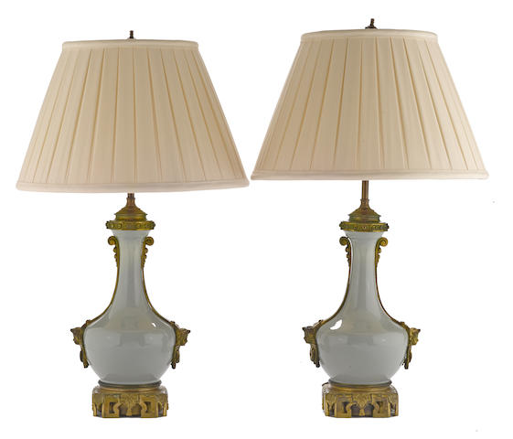 A pair of French gilt bronze mounted and celadon porcelain oil lamps