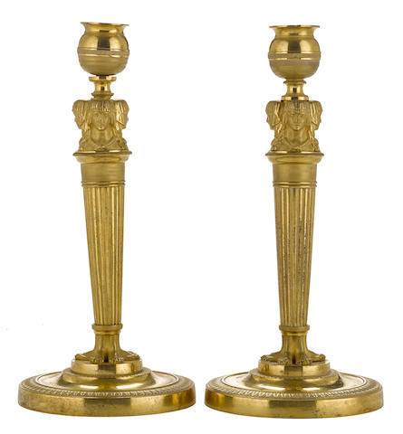 A pair of Empire style gilt bronze candlesticks with three addorsed figures
