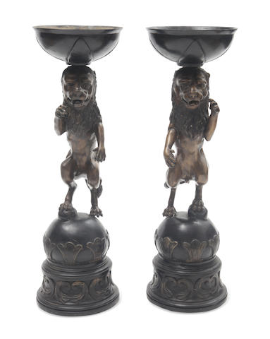 A pair of patinated bronze planters with lion supports