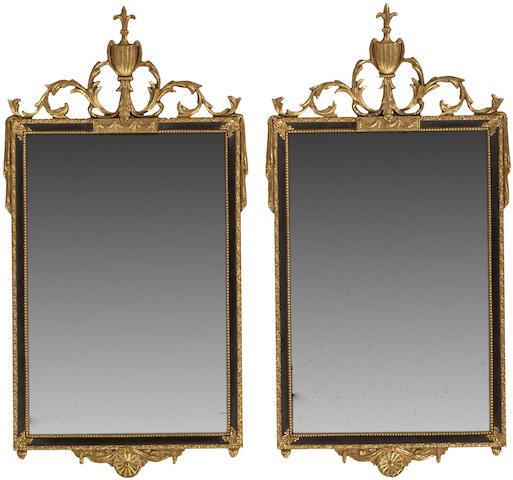 A pair of Louis XVI style parcel ebonized giltwood mirrors
