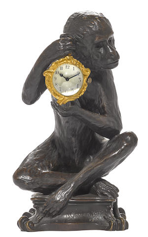 A French patinated bronze monkey holding a watch
