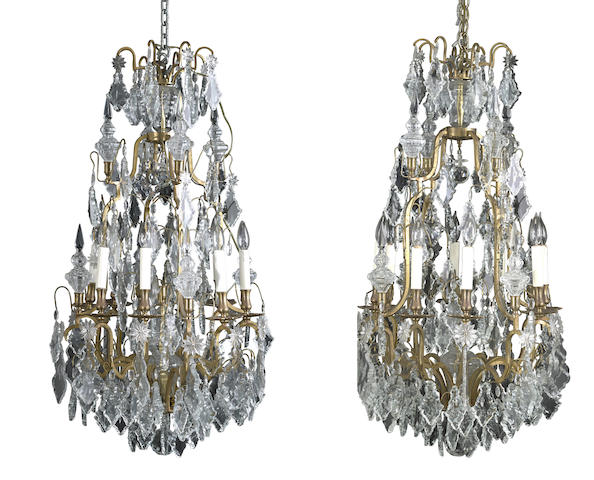 A pair of Rococo style cut and molded glass eight light chandeliers