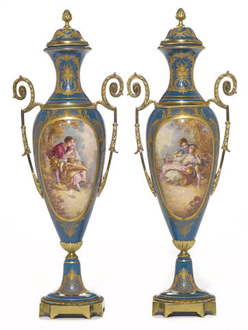 A pair of Sèvres style earthenware cast brass mounted covered urns