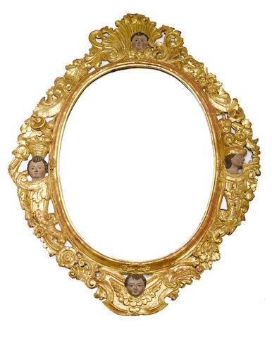 A paint decorated and giltwood oval mirror in the Spanish colonial taste