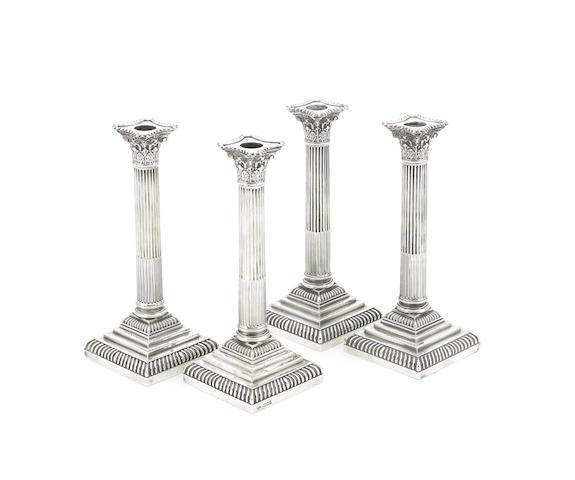 A matched set of four Edwardian silver Corinthian column candlesticks