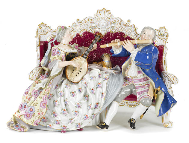 A Meissen porcelain figural group of two musicians seated on a settee