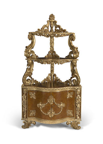 An Italian Rococo style parcel gilt and paint decorated corner cupboard
