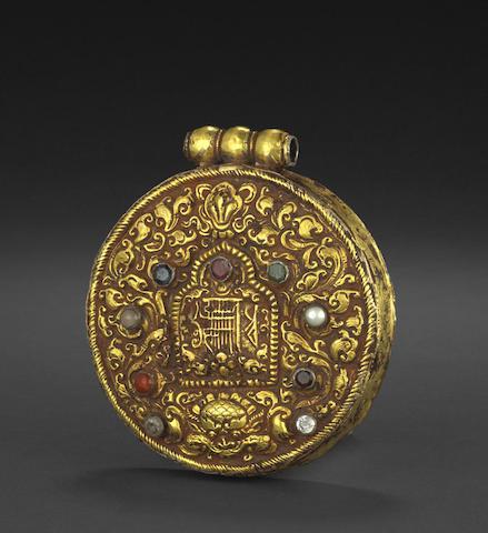 A gilt metal Kalachakra amulet with inset navaratna stones