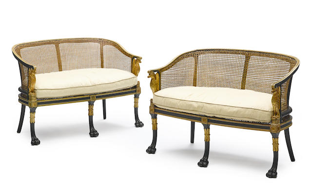A pair of Regency style parcel gilt, ebonized and cane paneled settees