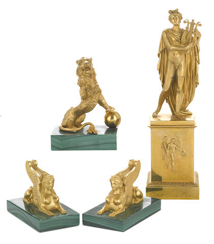A French gilt bronze figure of Apollo and three gilt bronze and malachite paperweights
