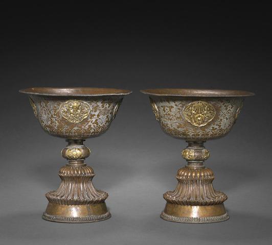 A pair of Tibetan copper alloy repoussé butter lamps