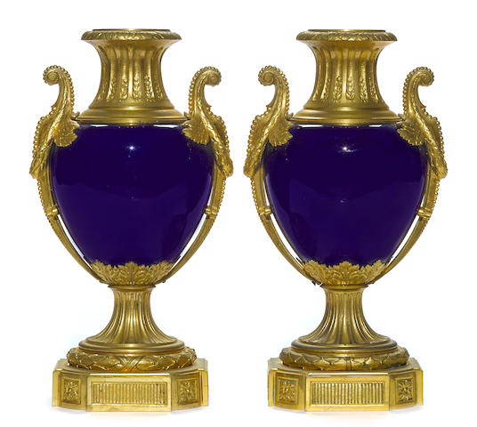 A pair of Louis XVI style gilt bronze mounted porcelain urns