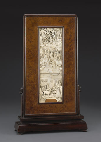 An ivory rectangular plaque mounted in a wood table screen