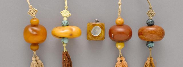 A group of pendants of amber and other materials