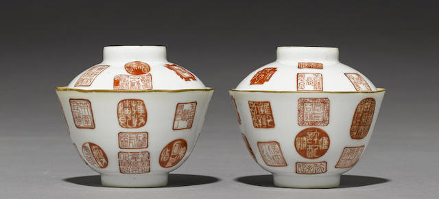 A pair of iron red and gilt decorated porcelain cups and covers