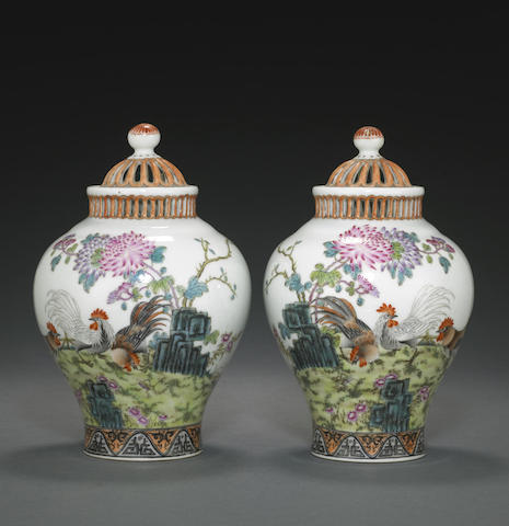 A pair of famille rose enameled jars and covers with reticulated decoration