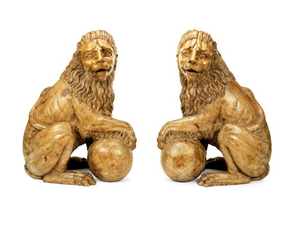 A pair of impressive decorative carved hardwood models of seated lions