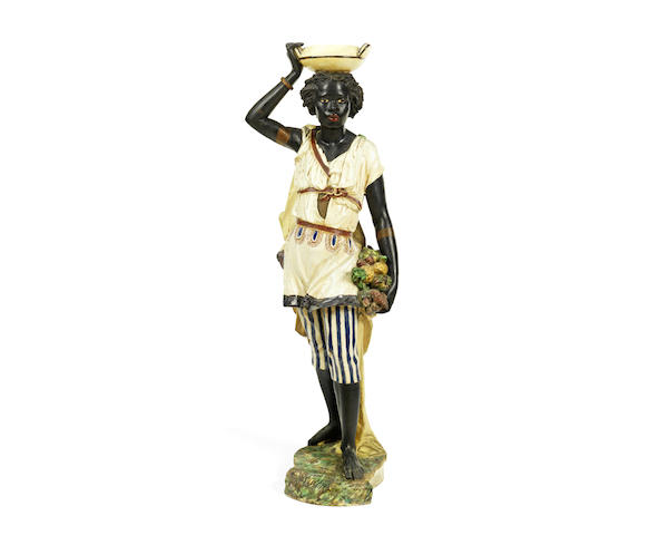 An early 20th century continental glazed and painted terracotta blackamoor torchiere figure