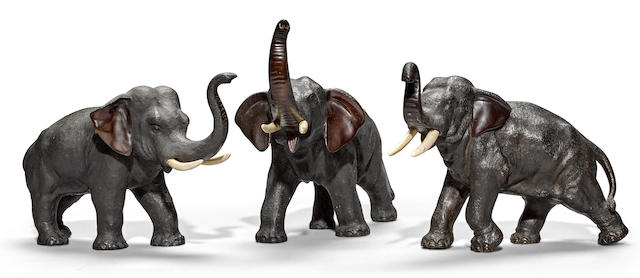 A group of three cast bronze elephants