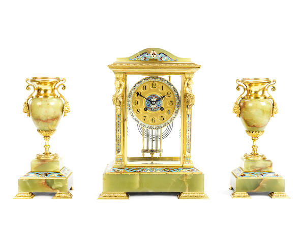 A late 19th century French gilt brass, champleve enamel and onyx four glass clock garniture