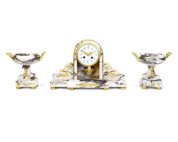An early 20th century French gilt bronze mounted mauve veined marble clock garniture