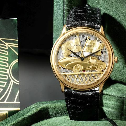 An 18K gold automatic semi-skeletonised motoring themed wristwatch