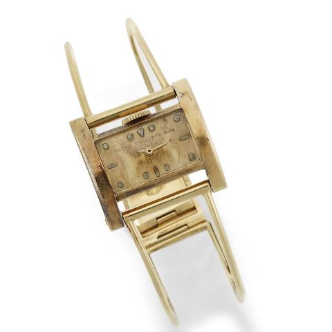 An unusual lady's 18K gold manual wind bangle watch