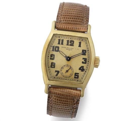 An 18K gold manual wind tonneau form wristwatch