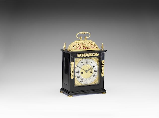 A late 17th century basket top ebony table clock