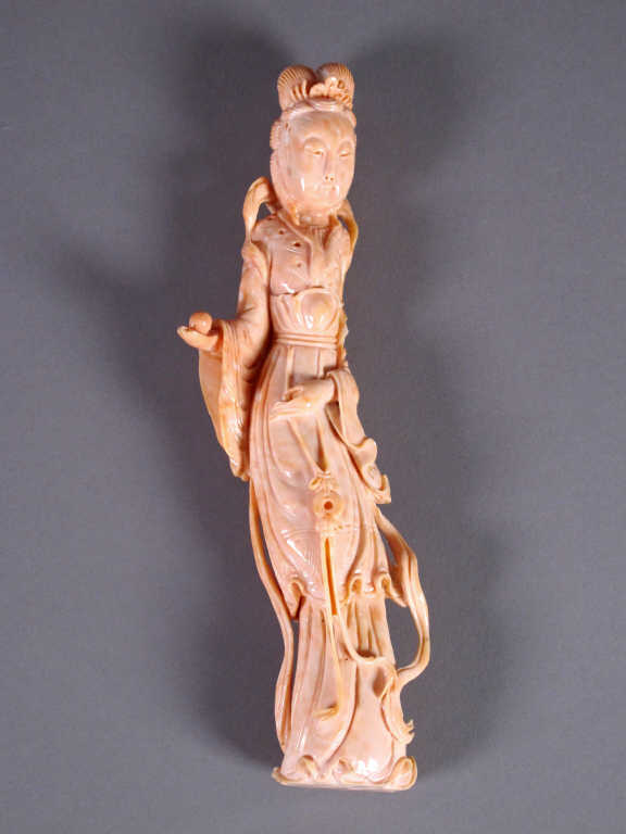 China statuette of young woman in pink coral, holding in his right hand a ball.