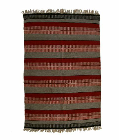 Flatwoven turning carpet with red/grey/white/black stripes.