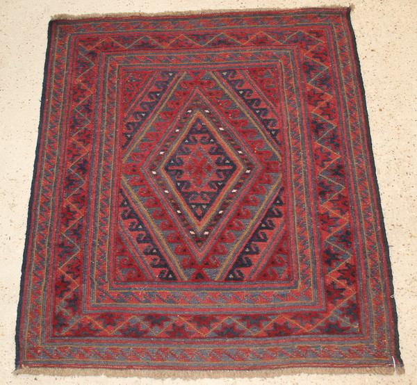 A contemporary red and blue ground tribal Gazak rug with diamond to the centre