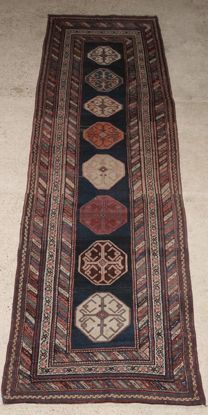 An Antique Caucasian blue ground runner with 8 octagons to the centre