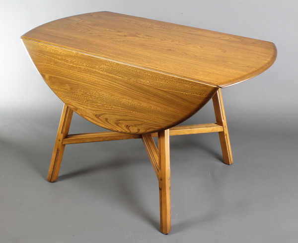 An Ercol light elm oval drop flap dining table raised on square supports with X framed stretcher