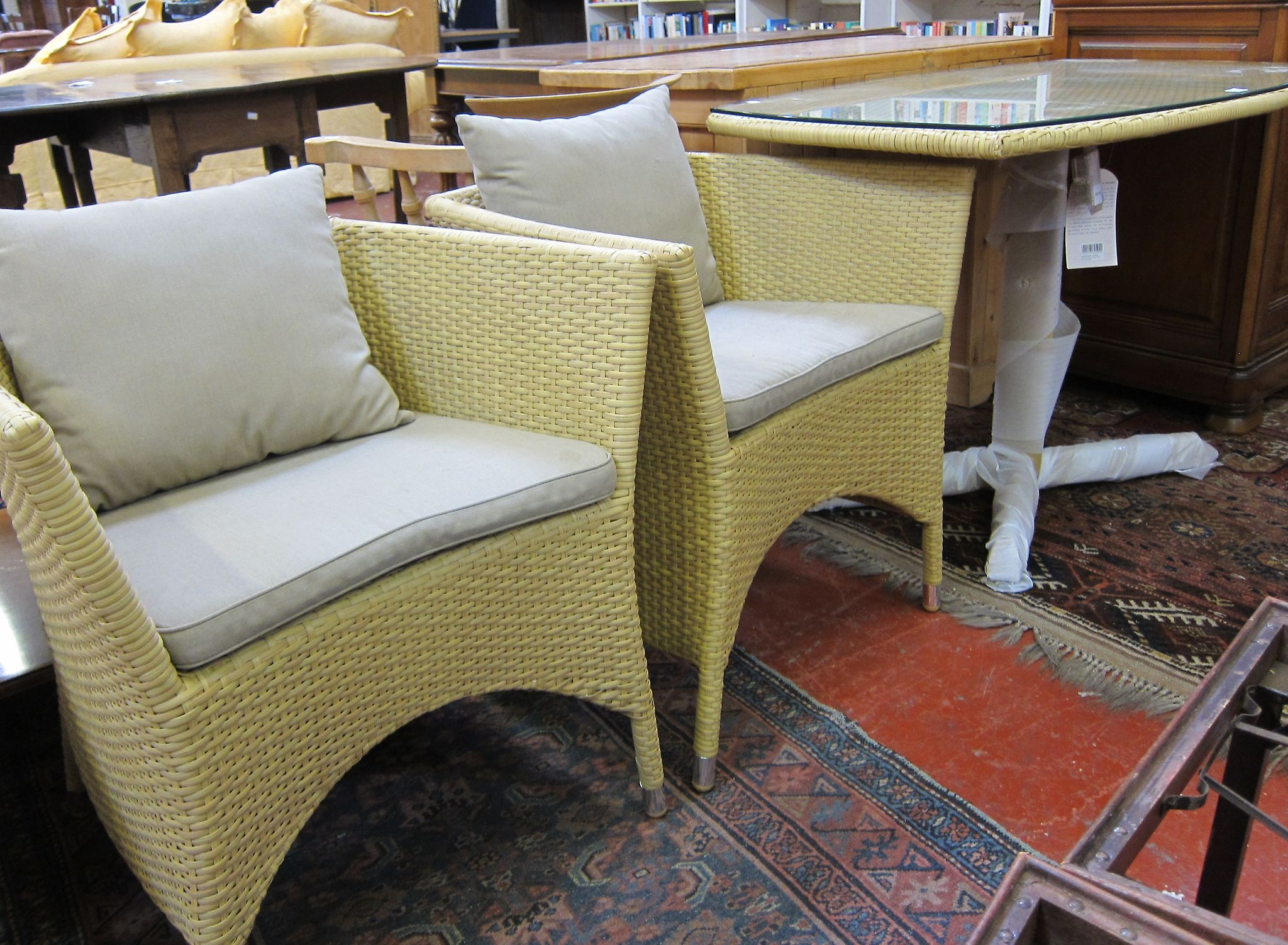 A woven cane effect table and two chairs