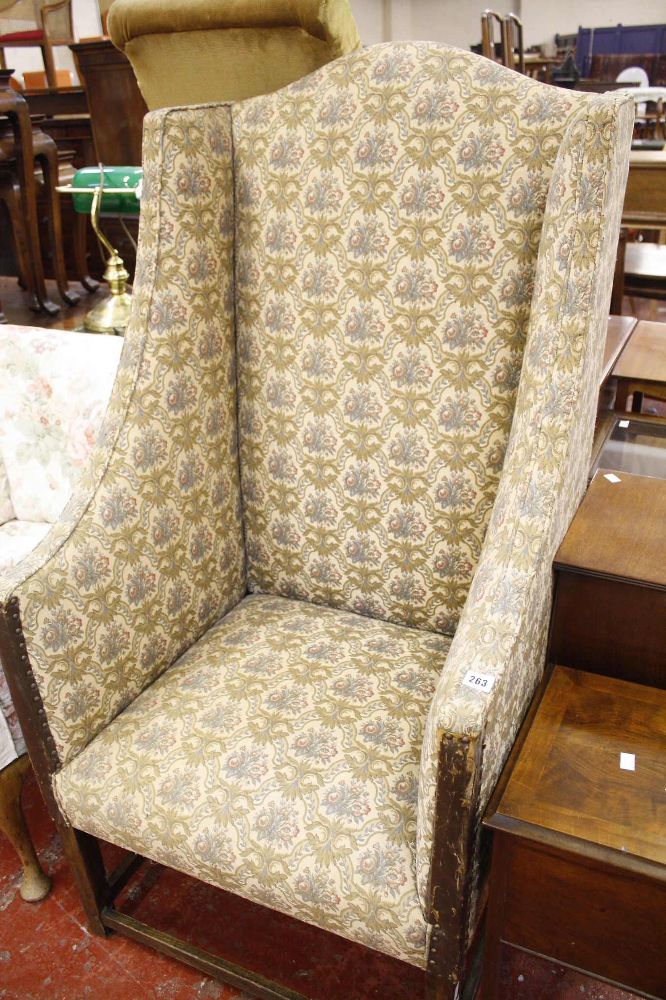 A walnut and upholstered wing armchair