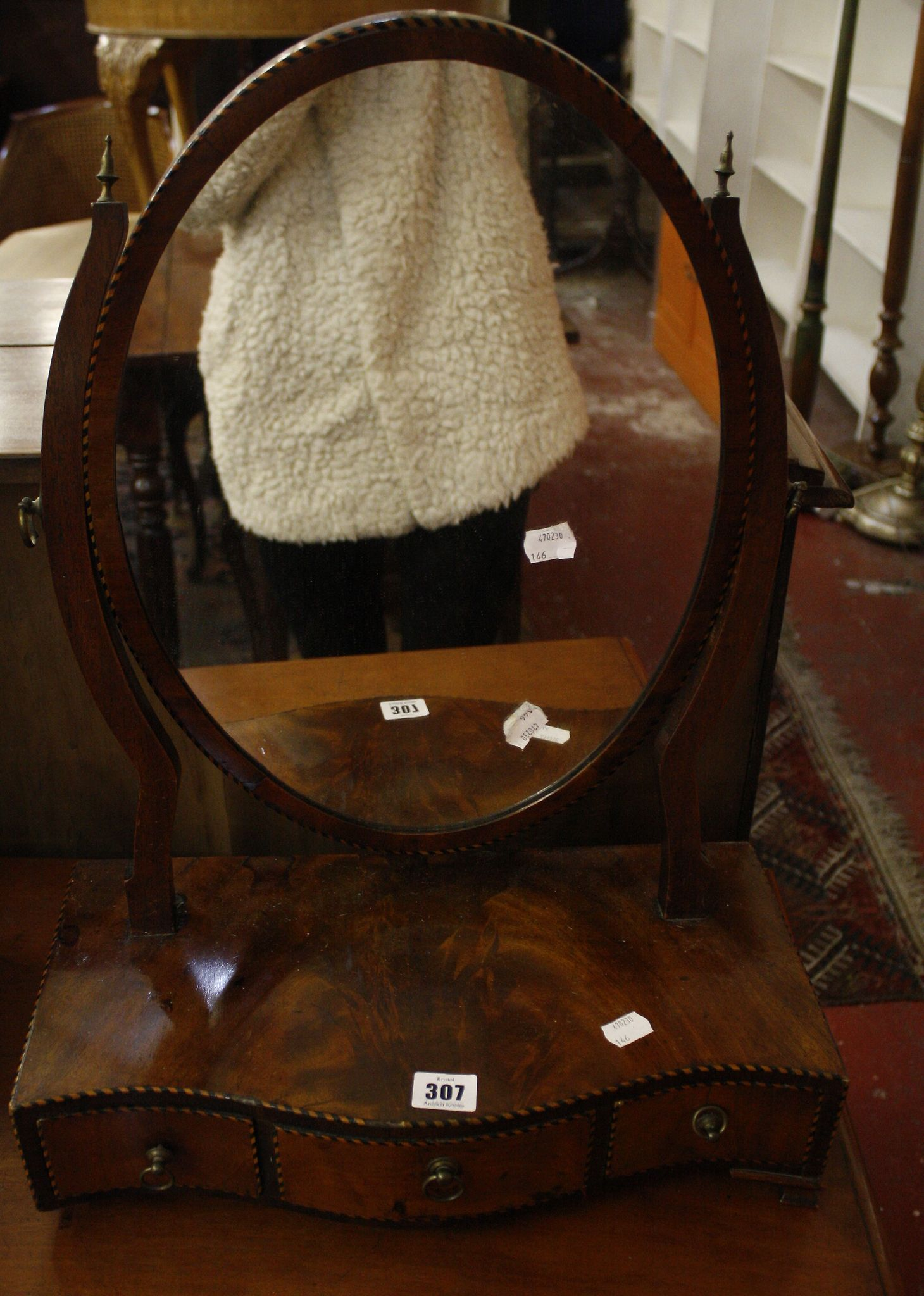A George III mahogany serpentine dressing mirror with three drawers
