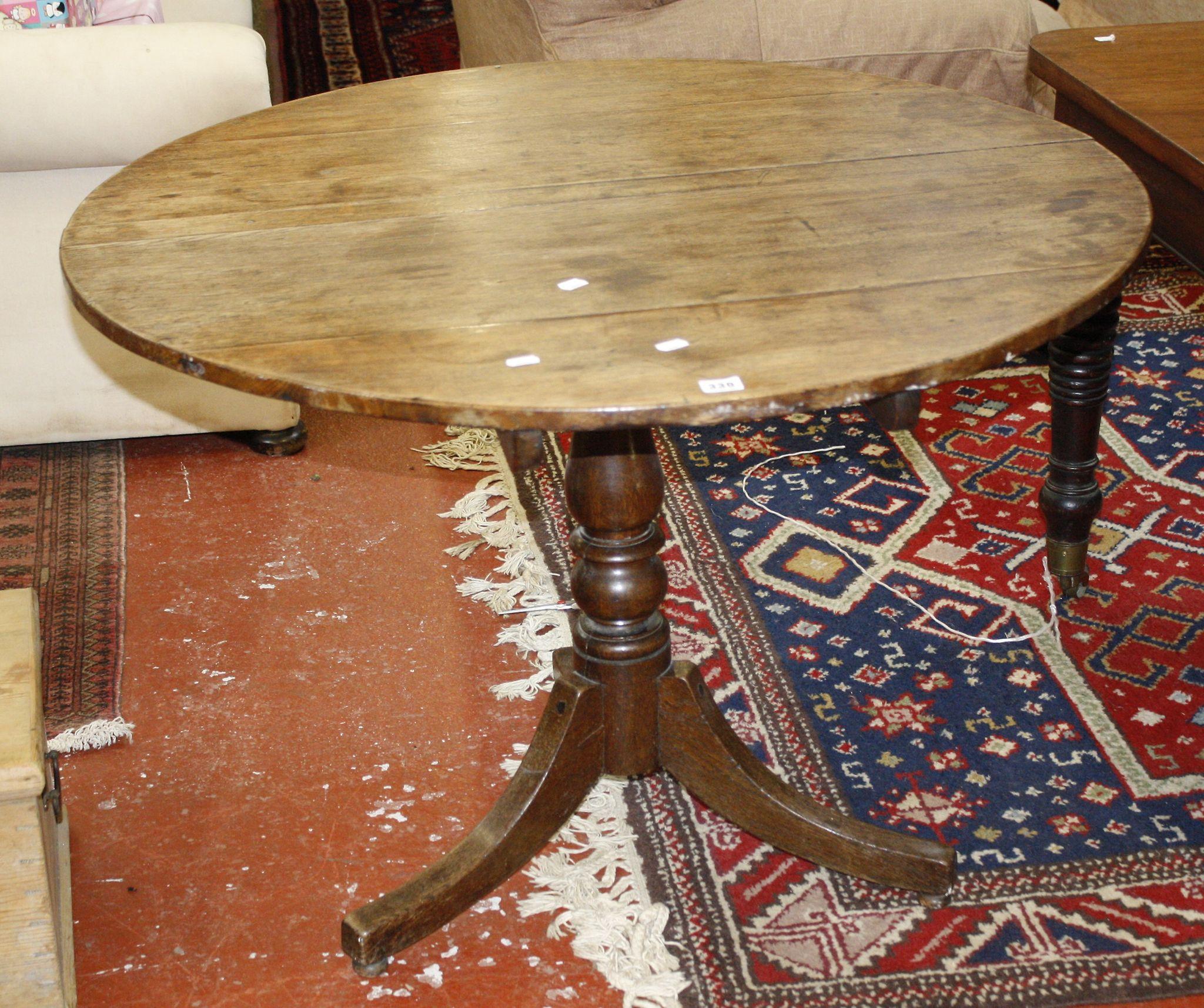 A 19th Century oak tilt top table on splayed legs 103cm diameter